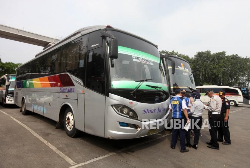 Petugas mengecek surat kendaraan bus dalam massa Pra Angkutan Lebaran 2018 di Terminal Kampung Rambutan, Jakarta, Senin (28/5).