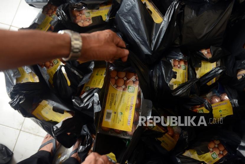 Petugas mengambil plastik untuk diberikan kepada warga saat pasar murah di Pasar Teluk Gong, Jakarta, Rabu (28/11).