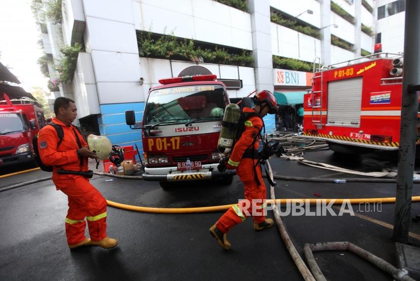 Sejumlah petugas damkar melakukan proses penyisiran pasca kebakaran di gedung Kementerian Perhubungan, Jakarta, Ahad (8/7).