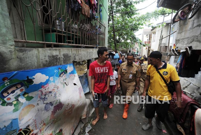 Gubernur DKI Jakarta Anies Baswedan(tengah) melakukan peninjauan ke wilayah yang terkena banjir di Gang Arus, Cawang, Jakarta Timur, Selasa (6/2).