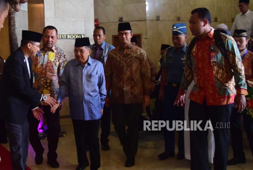 Wakil Presiden Republika Indonesia, Jusuf Kalla (kiri) bersama Gubernur DKI Jakarta, Anies Baswedan meninggalkan acara  pembukaan  pertemuan Ulama dan Da'I se-Asia Tenggara, Afrika dan Eropa yang diselanggarakan di Jakarta, Selasa (7/3).