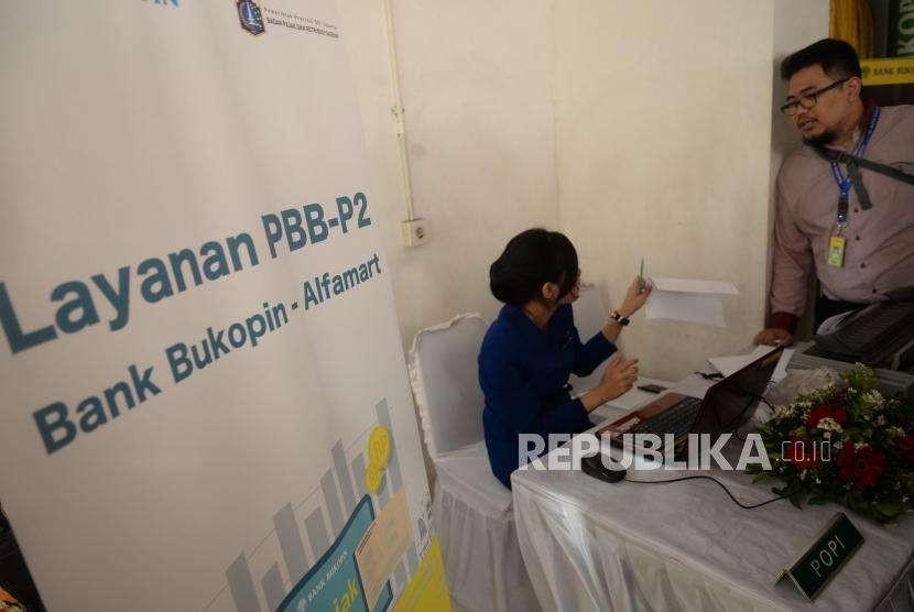 Layanan Pembayaran PBB. Petugas Bank Bukopin melayani pembayaran Pajak Bumi dan Bangunan untuk Perdesaan dan Perkotaan (PBB P2) saat peluncuran di Jakarta, Rabu (12/9).