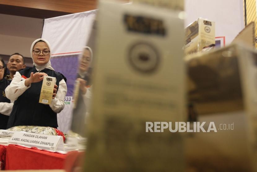 Kepala Badan Pengawas Obat dan Makanan Republik Indonesian (BPOM-RI) Penny K. Lukito memegang barang bukti temuan sejumlah makanan dan kopi dalam kemasan yang dinilai diedarkan secara ilegal di Jakarta, Senin (20/5).