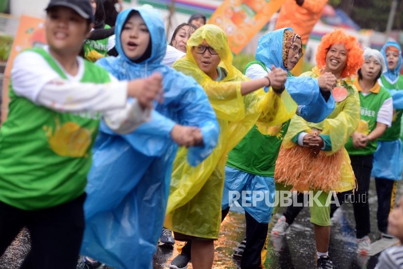 Olahraga Saat Hujan. Warga berolahraga menggunakan jas hujan pada hari bebas kendaraan bermotor di Jalan Jenderal Sudirman, Senayan, Jakarta.