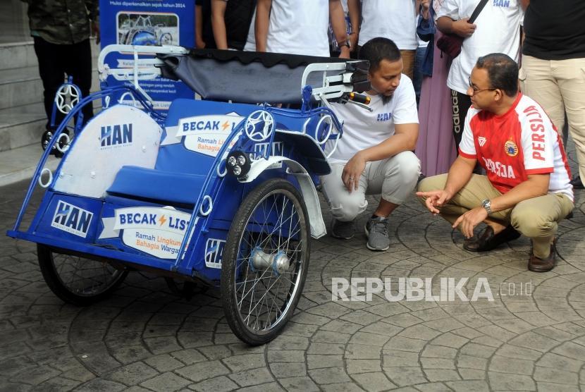 Gubernur DKI Jakarta Anies Baswedan melihat becak listrik yang diberikan oleh Wakil Ketua Umum DPP Partai Amanat Nasional Hanafi Rais (dari kanan) di Balaikota Jakarta, Ahad (11/3).