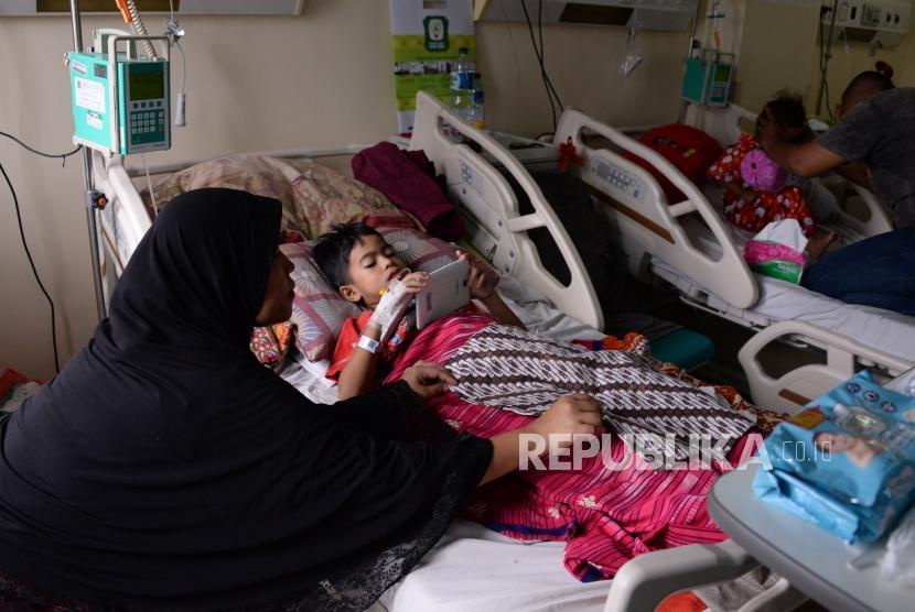 Seorang ibu menjaga anaknya yang terserang Demam Berdarah Dengue (DBD) yang dirawat di Rumah Sakit Umum (RSU) Kota Tanggerang Selatan, Banten, Selasa (29/1).