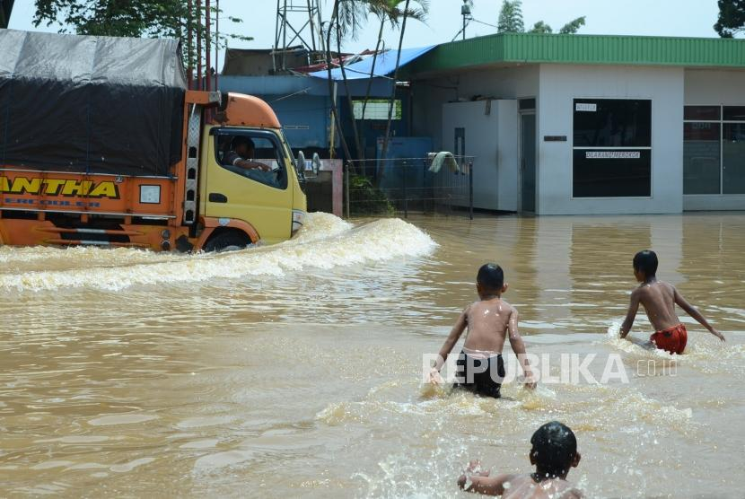 Banjir Bandung Selatan. Sejumlah anak menonton sebuah truk yang nekat melintasi genangan banjir yang merendam Jalan Anngadireja, Kecamatan Baleendah, Kabupaten Bandung, Senin (25/2).