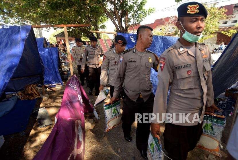 Sejumlah petugas kepolisian saat memberikan bantuan kepada pengungsi di Posko pengungsian Lapangan Masjid Agung Darussalam , Palu, Sulawesi Tengah, Jumat (5/10).