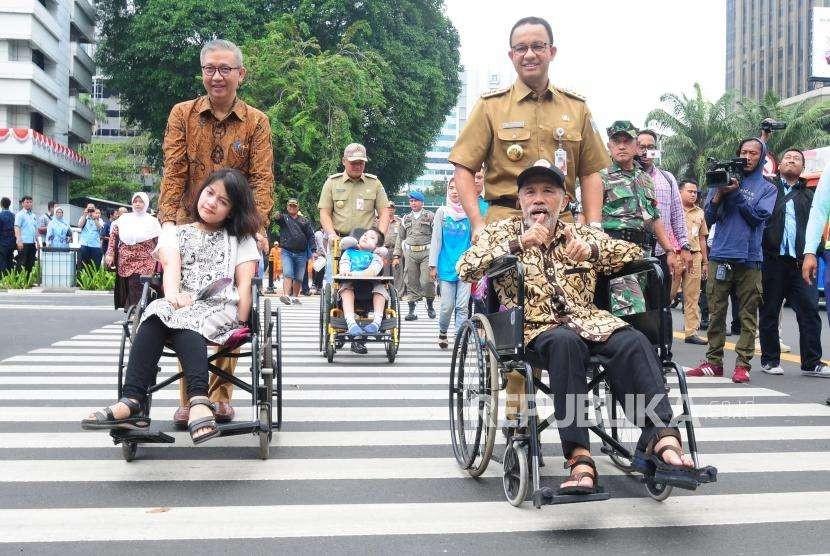 Gubernur DKI Jakarta Anies baswedan bersama Direktur Utama PT Transportasi Jakarta Budi Kaliwono mengantarkan penyandang disabilitas menyeberangi pelican crossing di Jalan MH Thamrin, Jakarta Pusat, Selasa (4/9).