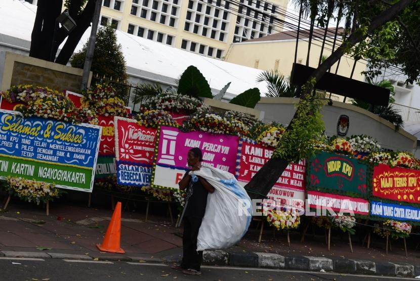 Seorang pemulung melintas di dekat karangan bunga yang terpasang di depan Gedung Komisi Pemilihan Umum (KPU), Jakarta, Ahad (21/4).