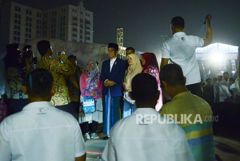 Presiden RI Joko Widodo (Jokowi) berfoto bersama masyarakat saat menghadiri malam puncak peringatan Hari Santri Nusantara, di Lapangan Gasibu, Kota Bandung, Ahad (21/10).