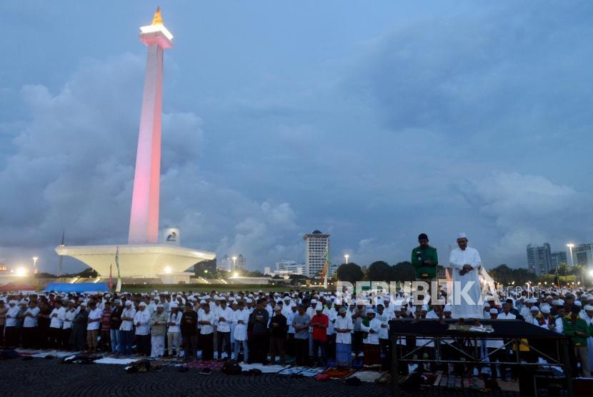 Shalat Maghrib Berjamaah. Sejumlah umat muslim melaksanakan shalat Maghrib berjamaah di Monas, Jakarta, Kamis (21/2).
