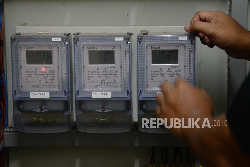 Petugas memeriksa meteran listrik di Rumah Susun Jatinegara Barat, Jakarta, Senin (13/11).
