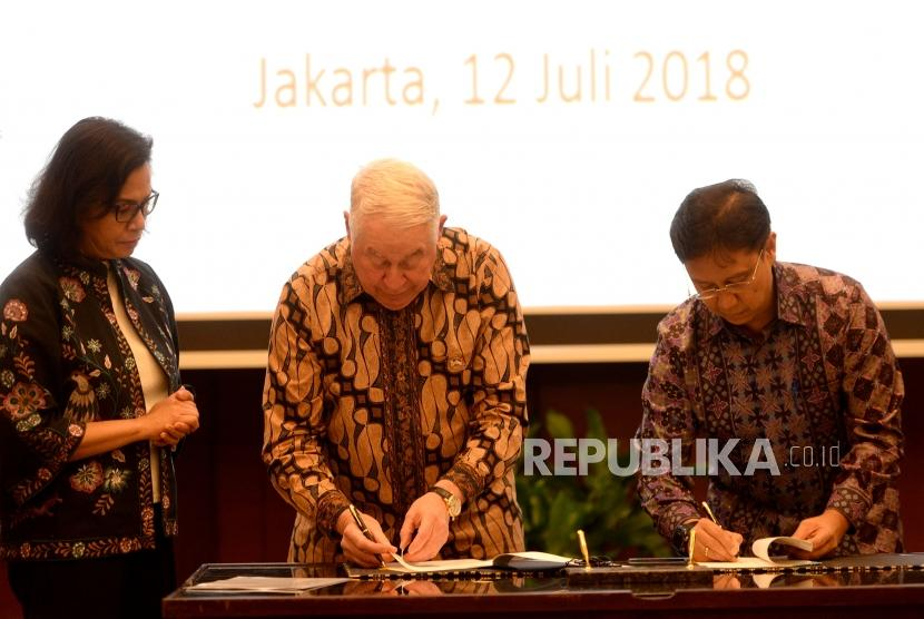 PT Inalum President Director Budi Gunadi Sadikin and CEO Freeport-McMoran Inc Richard Adkerson sign  the divestment agreement of PT Freeport Indonesia shares, witnessed by Minister of Finance Srri Mulyani (from the right) at the Ministry of Finance, Jakarta, Thursday (July 12).