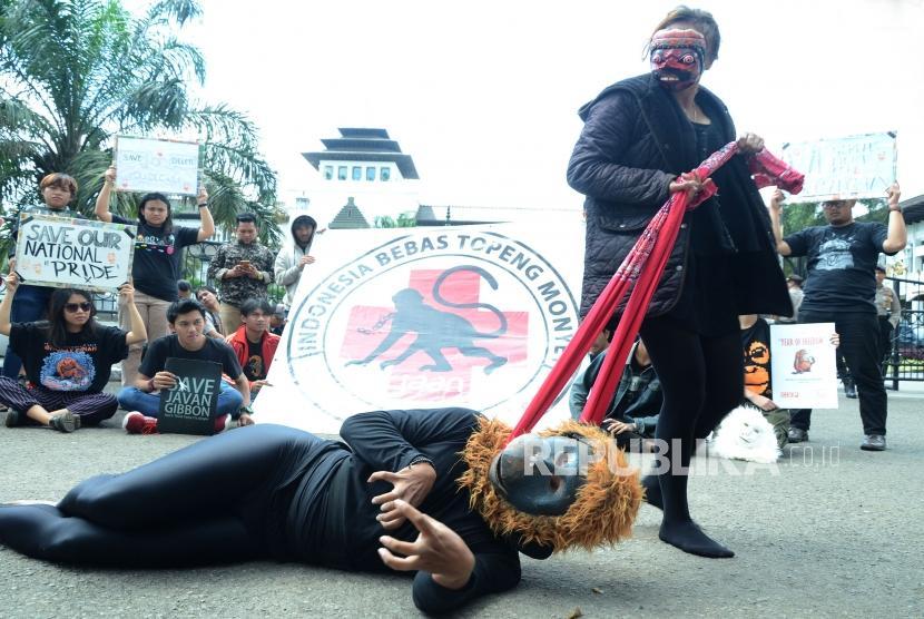 Aksi teaterikal yang menggembarkan penderitaan monyet yang dipekerjakan saat aksi Air Mata Topeng Monyet yang digelar Jakarta Animal Aid Network (JAAN) dalam rangka Peringatan Hari Primata Nasional, di depan Gedung Sate, Kota Bandung, Selasa (30/1).