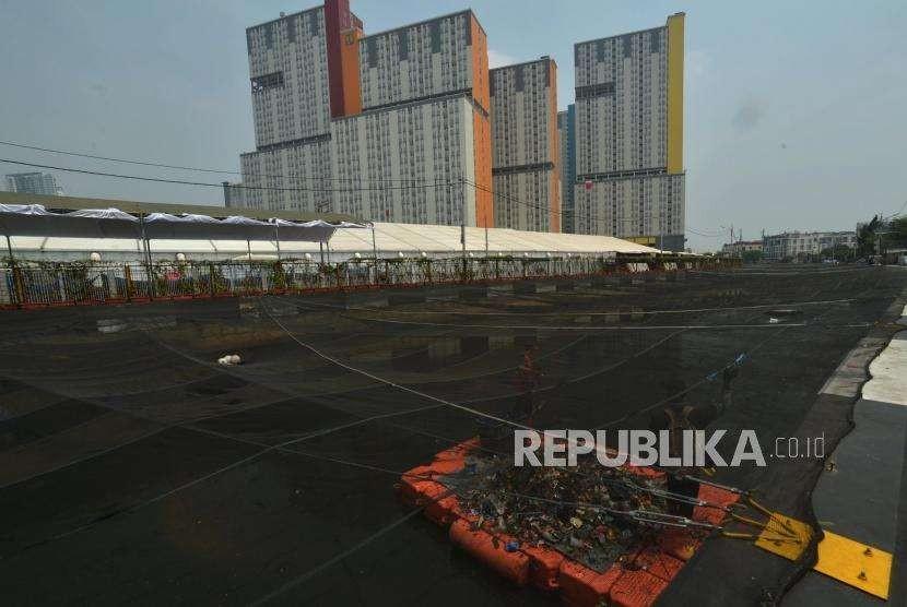 Petugas PPSU membersihkan Kali Item/ Kali Sentiong yang ditutupi jaring di kawasan Wisma  Atlet, Kemayoran Jakarta Pusat, Jumat (5/10).