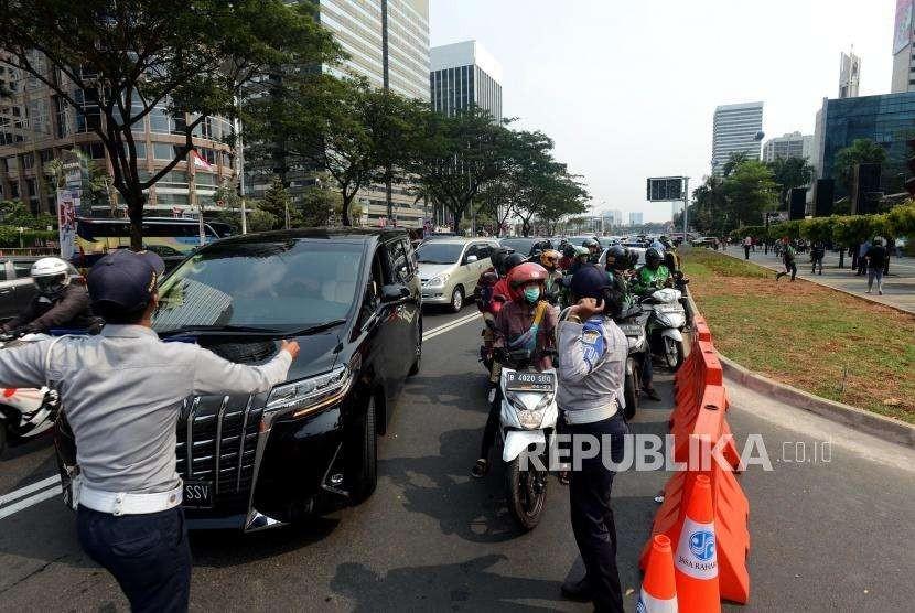 Sejumlah petugas kepolisian mengatur lalu lintas sebelum upacara pembukaan Asian Games 2018 di kawasan Gelora Bung Karno, Jakarta, Sabtu (18/8).