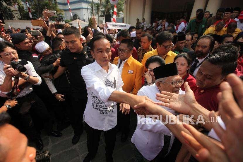 Calon presiden Joko Widodo (kiri) didampingi calon wakil presiden Ma'ruf Amin (kanan) bersalaman dengan para relawan seusai deklarasi di Gedung Joang, Jakarta, Jumat (10/8).