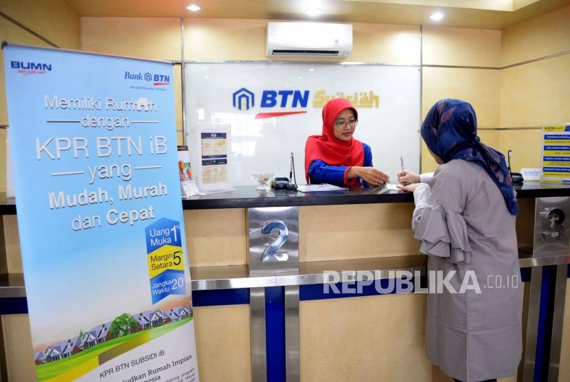 Petugas melayani transaksi nasabah di kantor layanan BTN Syariah, Jakarta.