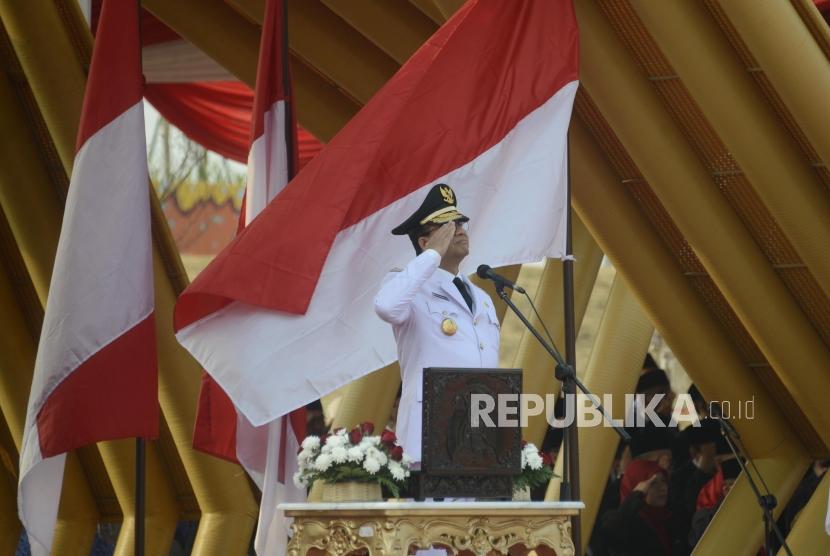 Gubernur DKI Jakarta Anies Baswedan selaku inspektur upacara menghormati bendera saat peringatan hari kemerdekaan RI di Pantai Maju, Jakarta, Sabtu (17/8).