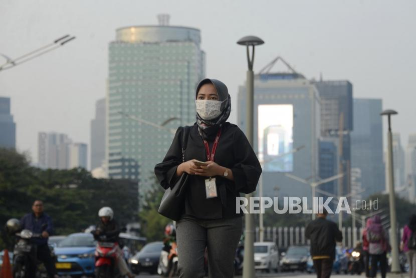 Warga menggunakan masker dengan latar belakang suasana gedung bertingkat yang diselimuti asap polusi di kawasan Sudirman, Jakarta, Senin (29/7).