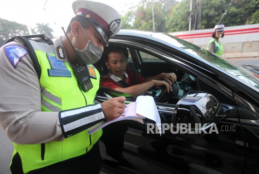 Polisi menilang pengendara bernomor polisi genap saat sistem ganjil genap di Kawasan Pancoran, Jakarta, Rabu (1/8).