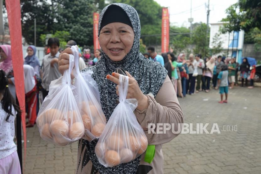 Operasi Pasar Telur Ayam. Warga mengantri membeli telur ayam saat operasi pasar di Toko Tani Indonesia Center (TIIC), Jakarta, Kamis (19/7).