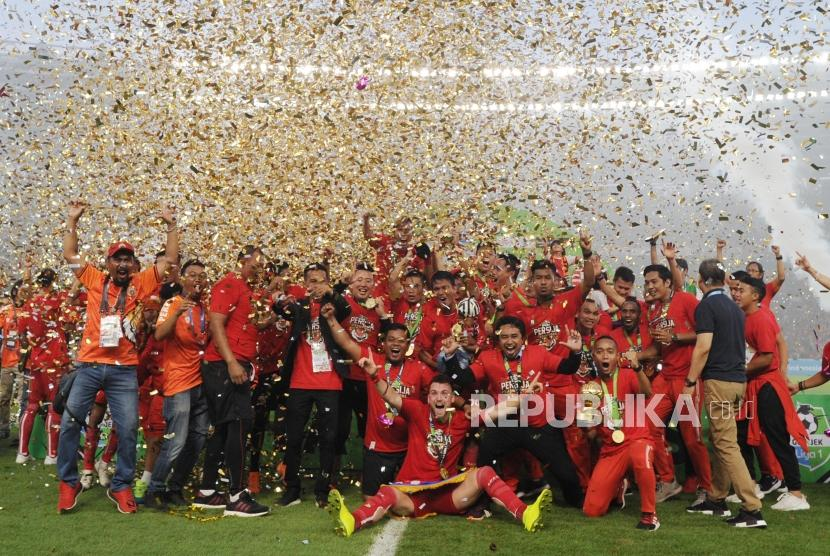 Pemain dan pengurus Persija Jakarta mengangkat piala seusai mengalahkan Mitra Kukar dalam laga Liga 1 2018 di di Stadion Utama Gelora Bung Karno, Jakarta, Ahad (9/12).