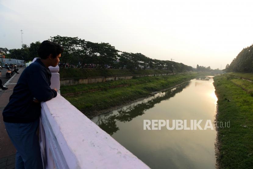 Warga melihat aliran sungai Banjir Kanal Timur di kawasan Duren Sawit, Jakarta Timur, Kamis (25/10).