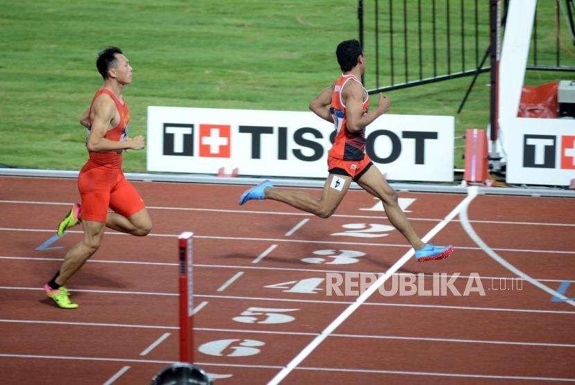Atlet lari Indonesia Lalu Muhammad Zohri (kanan) tiba di garis finish pada babak kualifikasi cabang olahraga atletik Asian Games 2018 kategori lari 100 meter putra di Stadion Utama Gelora Bung Karno, Jakarta, Sabtu (25/8).