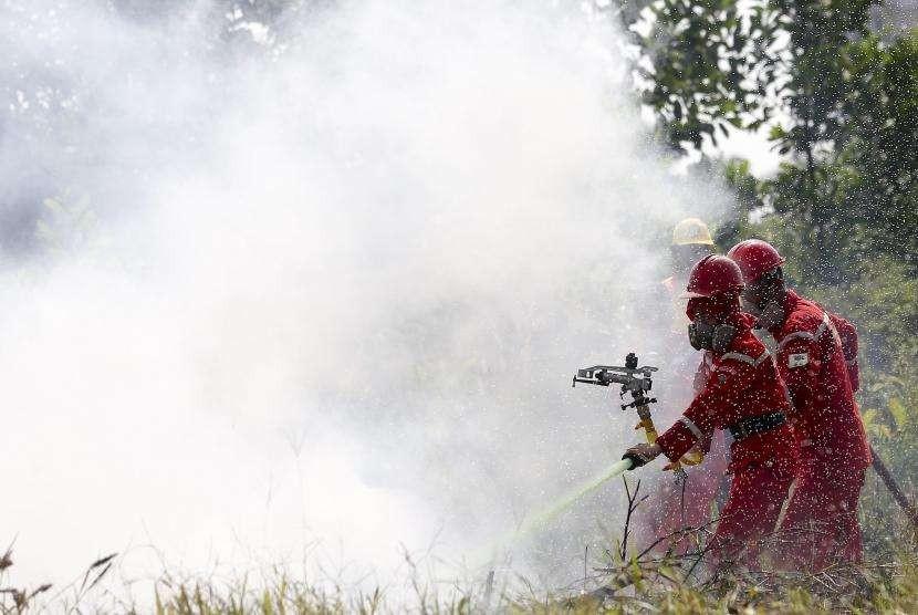 Petugas dari Manggala Agni Daops Banyuasin melakukan pemadaman kebakaran lahan saat simulasi pemadaman Kebakaran Hutan dan Lahan (Karhutla) di posko pemantau Pegayut, Ogan Ilir, Sumatera Selatan, Senin (30/7).