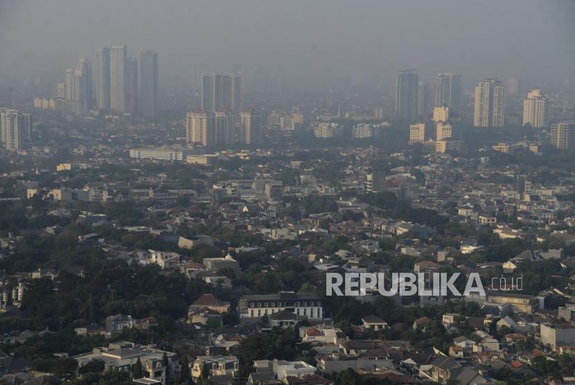 Suasana permukiman dengan latar belakang gedung bertingkat yang diselimuti asap polusi di Jakarta, Rabu (31/7).