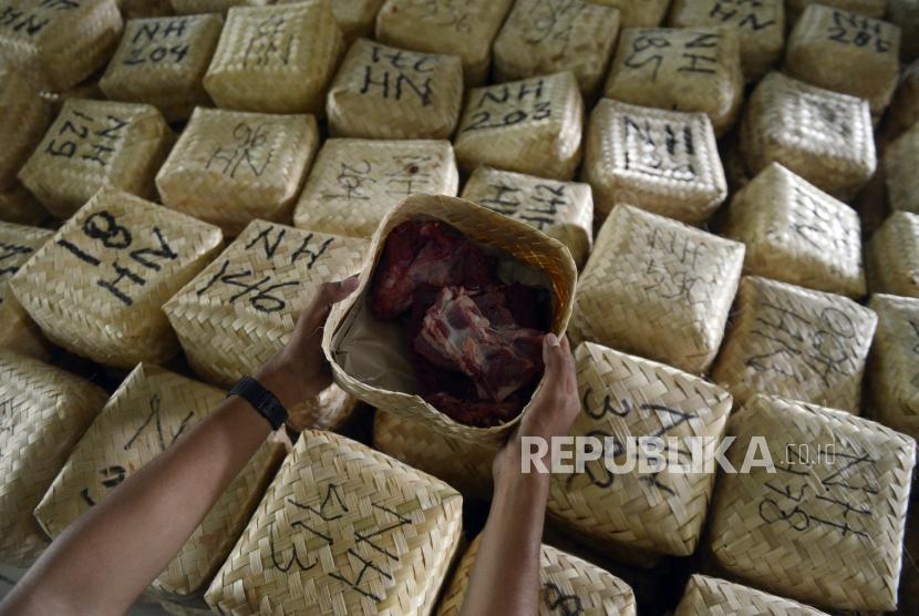 Panitia merapikan besek bambu berisi daging kurban