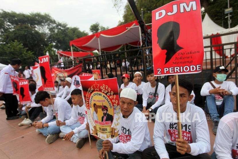 Relawan Jokowi-Ma'ruf Amin berkumpul untuk menunggu kedatangan capres petahana Joko Widodo bersama cawapres Ma'ruf Amin di Tugu Proklamasi, Jakarta, Jumat (21/9).