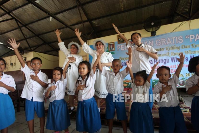 Ibu guru kembar Rian dan Rossi belajar menari bersama para siswa di Sekolah Kartini Kampung Lodan, Jakarta, Senin (26/11).