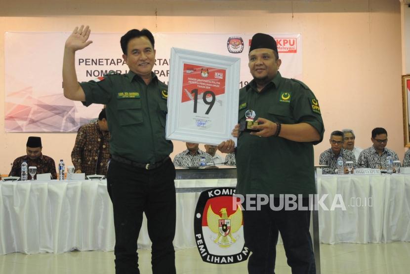Ketua  Umum Partai Bulan Bintang Yusril Ihza Mahendra bersama Sekjen PBB Ferry Afriansyah Noor menunjukan nomor urut sembilan belas saat acara Pengundian Nomor Urut Peserta Pemilu 2019 di Kantor KPU, Jakarta, Ahad (18/2).