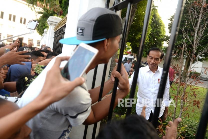 Menyapa Warga Jogja. Presiden Joko Widodo menyapa warga yang mengantre pembagian paket lebaran di Gedung Agung, Yogyakarta,  Kamis (6/6/2019).