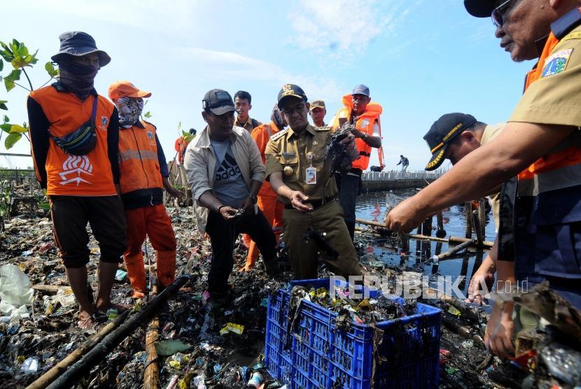 Gubernur DKI Jakarta Anies Baswedan mengambil sampah saat meninjau sampah yang menumpuk di Muara Angke, Jakarta Utara Senin (19/3).