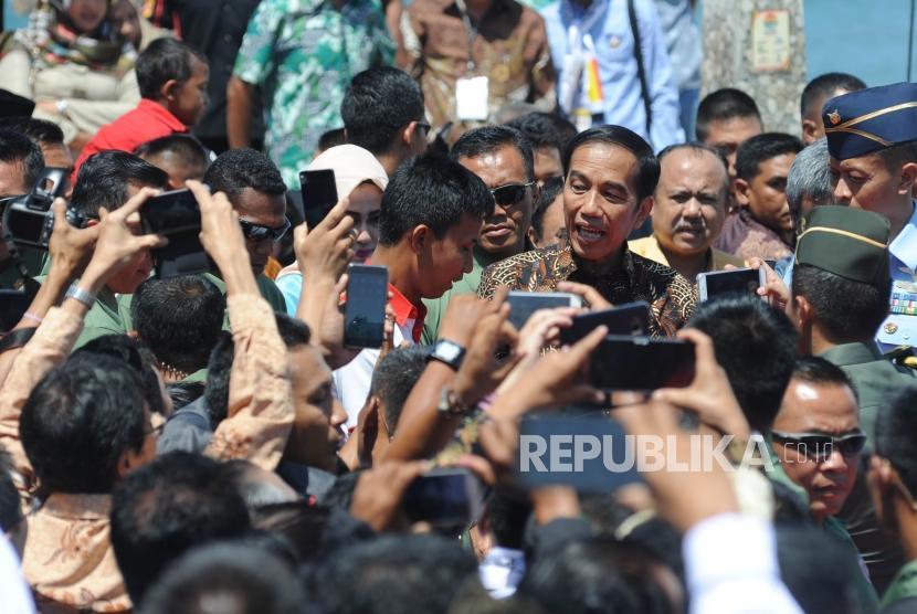 Presiden Republik Indonesia Joko Widodo berjalan menyapa warga usai memberikan sambutan dalam acara puncak peringatan Hari Pers Nasional 2018 di Danau Cimpago, Kota Padang, Provinsi Sumatra Barat, 9 Februari 2018.