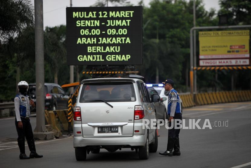 Petugas mengarahkan kepada pengendaran mobil bernomor polisi ganjil saat hari pertama pemberlakuan sistem ganjil genap di Gerbang Tol Bekasi Barat 1, Bekasi, Jawa Barat, Senin (12/3).