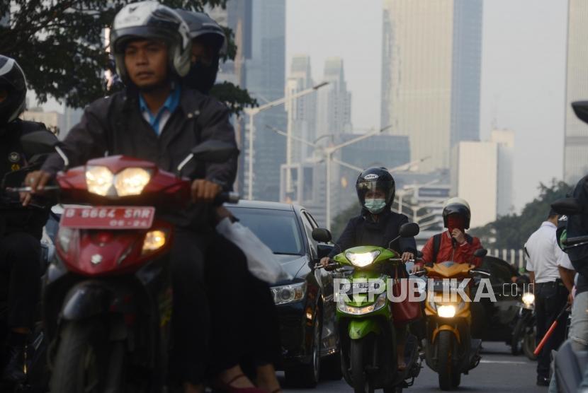Pengendara motor menggunakan masker dengan latar belakang suasana gedung bertingkat yang diselimuti asap polusi di kawasan Sudirman, Jakarta, Senin (29/7).