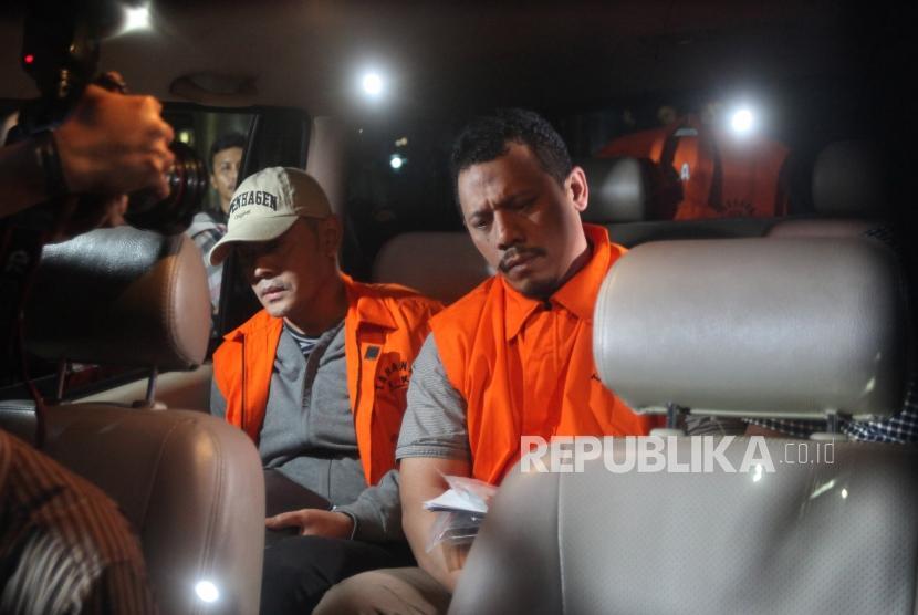 Tersangka kasus suap fasilitas sel mewah dan izin keluar napi korupsi Fahmi Darmawansyah (kiri) bersama Andri Rahmad (kanan) terpidana umum memakai rompi tahanan didalam mobil seusai menjalani pemeriksaan di Gedung KPK, Jakarta, Sabtu (21/7).