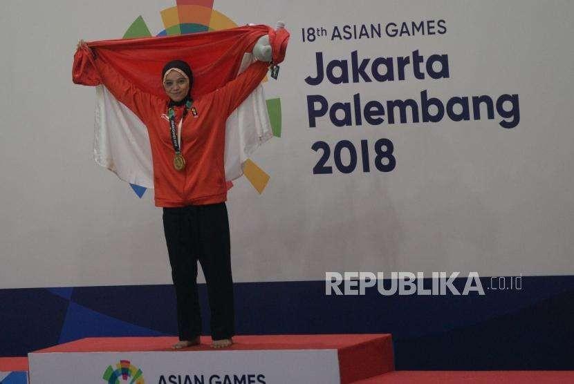 Pesilat Indonesia Sarah Tria Monita berfoto pada penyerahan medali usai menang bertanding melawan pesilat Laos Nong Oy Vongphakdy pada babak final cabang pencak silat putri kelas C 55-60 kg Asian Games 2018 di Padepokan Pencak Silat,TMII, Jakarta, Senin (27/8).