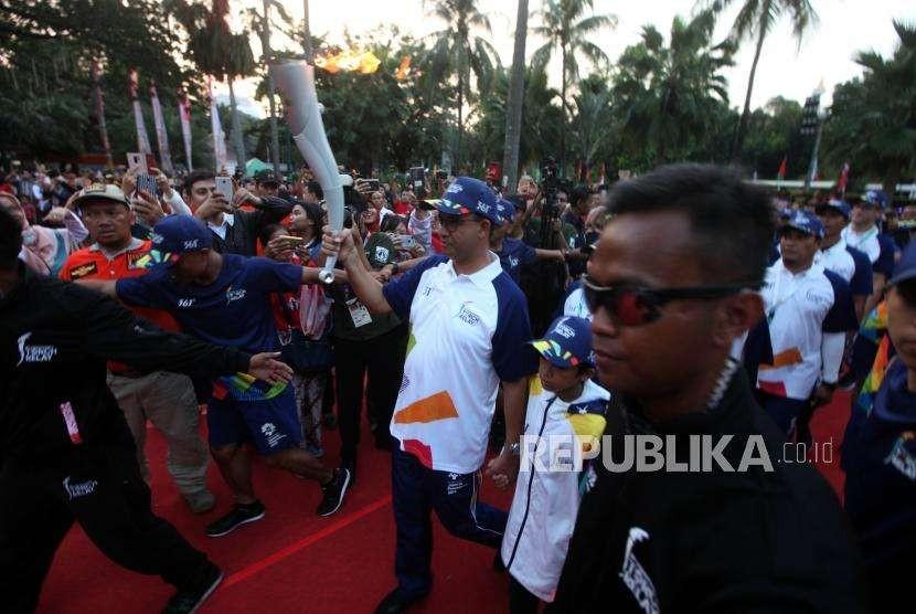 Gubernur DKI Jakarta Anies Baswedan membawa obor saat Torch Relay Asian Games 2018 di Balai Kota, Jakarta, Rabu (15/8).