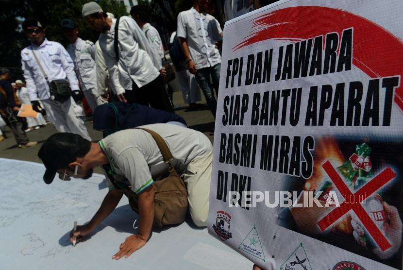 Aksi Dukung Pelepasan Saham Bir. Sejumlah massa PA 212 dan Jawara Betawi membubuhkan tanda tangan saat melakukan aksi di Jalan kebon Sirih, Jakarta, Jumat (8/3).