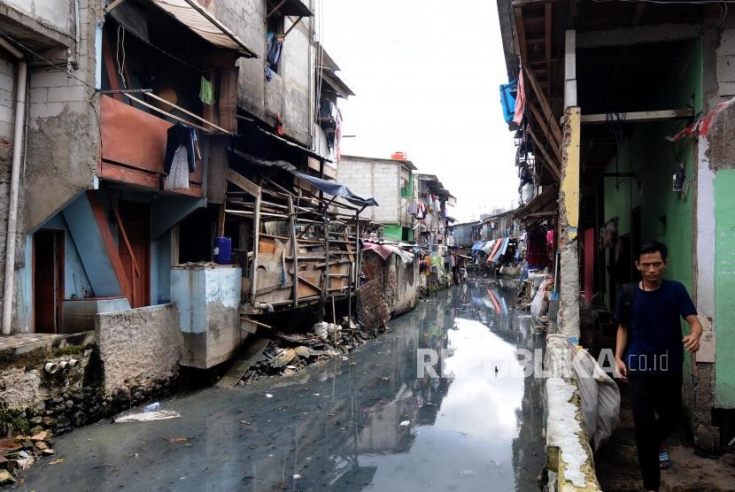Warga melintas di kawasan pemukiman kumuh di Kebon Melati, Tanah Abang, Jakarta Pusat, Selasa (28/11).