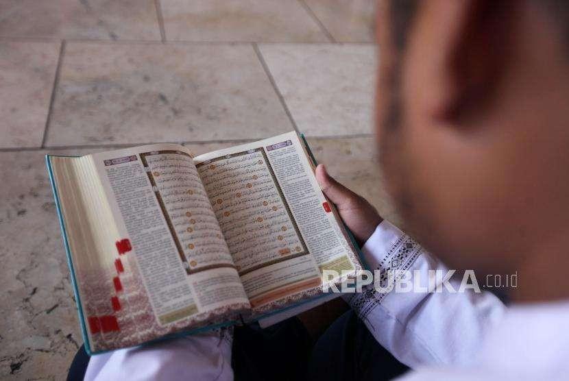 Seorang pelajar membaca Alquran seusai salat Jumat di Masjid Istiqlal, Jakarta.