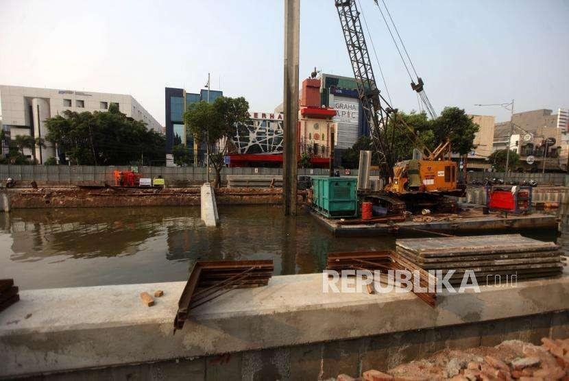 Pekerja dari Dinas Sumber Daya Air Pemerintah Provinsi (Pemprov) DKI Jakarta mengoprasikan alat berat saat memasang turap di Kali Ciliwung lama, Jalan Veteran, Jakarta, Rabu (10/10).