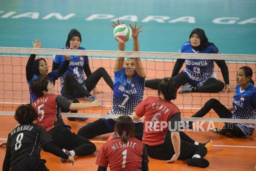 Atlet bola voli duduk Indonesia Anissa Tindy Lestary berusaha mengembalikan bola saat bertanding melawan tim bola voli duduk Jepang pada babak perebutan juara 3 voli duduk putri Asian Para Games 2018 di Gelora Bung Karno, Jakarta, Kamis (11/10).