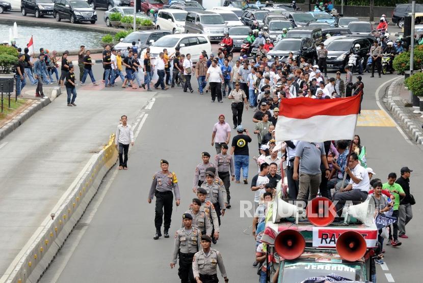 Sejumlah pengemudi taksi online yang tergabung dalam Aliansi Nasional Driver Online (ALIANDO) melakukan aksi long march menuju Kantor Kementerian Perhubungan di Jalan Medan Merdeka Barat, Jakarta, Senin (22/1).